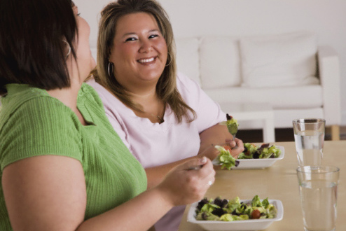 Two girls eating salads
